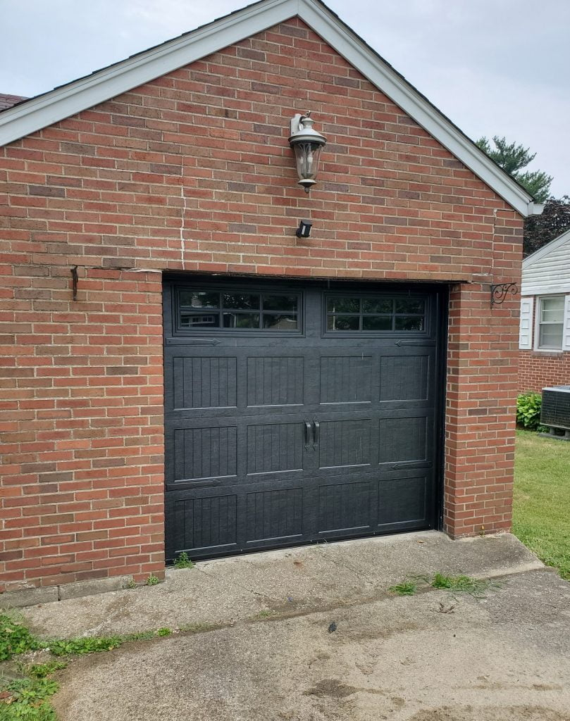 Black painted Carriage Style garage door with windows and hardware.